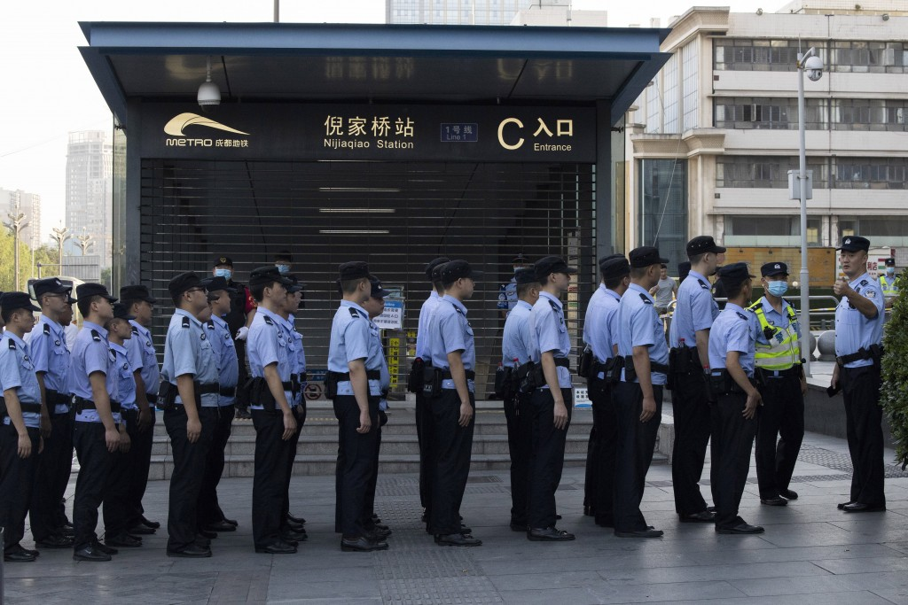 Chinese policemen prepares for duty around a neighborhood sealed off before the official closure of the United States Consulate in Chengdu in southwes...