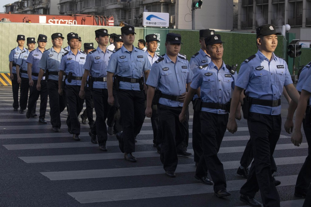 Chinese policemen prepare for duty around a neighborhood sealed off before the official closure of the United States Consulate in Chengdu in southwest...