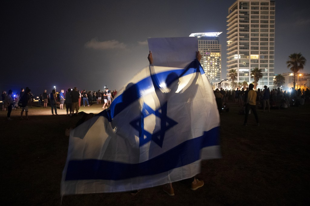 File - In this Saturday, July 25, 2020 file photo, people wave the Israeli national flag during a protest against Israel's Prime Minister Benjamin Net...