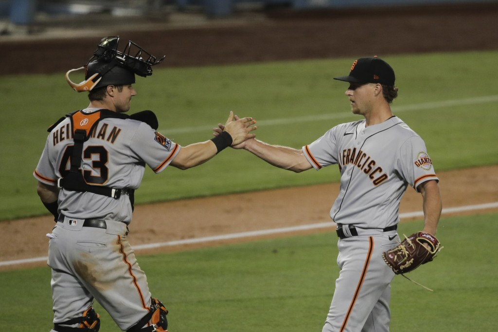 San Francisco Giants relief pitcher Trevor Gott, right, and catcher Tyler Heineman celebrate the team's 3-1 win over the Los Angeles Dodgers in a base...