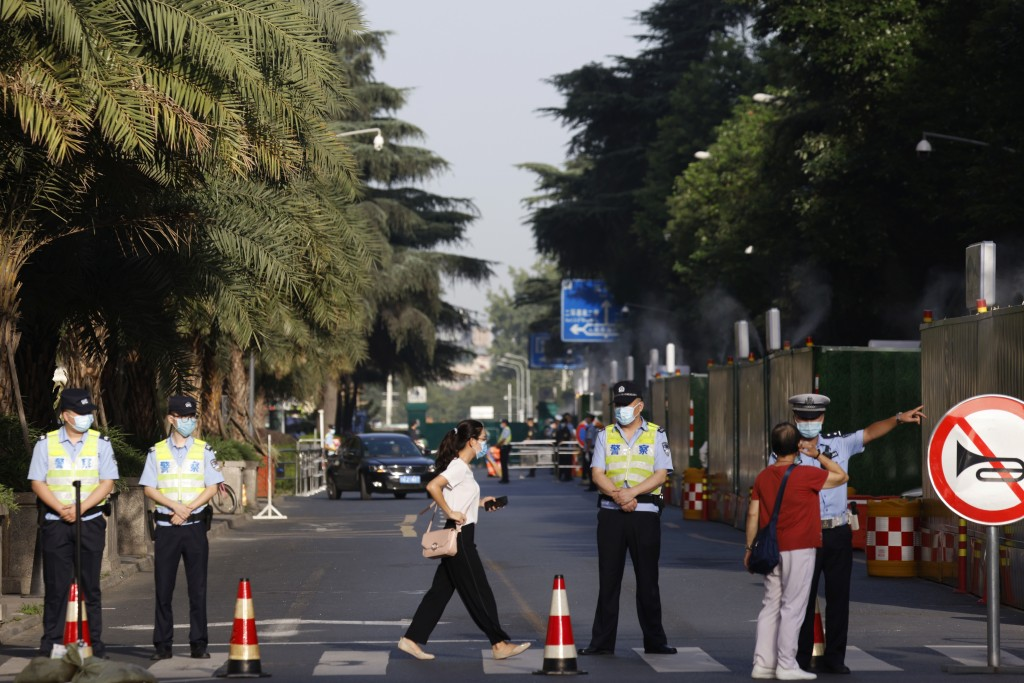 Chinese policemen direct residents away from a neighborhood sealed off before the official closure of the United States Consulate in Chengdu in southw...