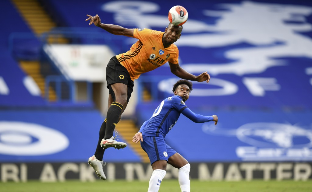 Chelsea's Willian, right, watches Wolverhampton Wanderers' Willy Boly leaping for a header during the English Premier League soccer match between Chel...