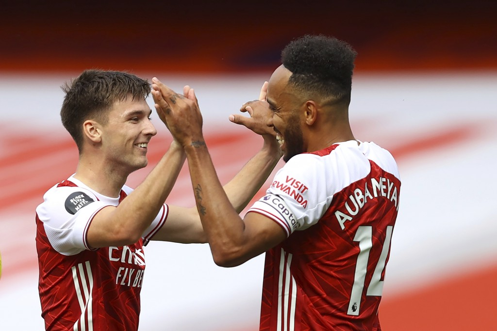 Arsenal's Kieran Tierney, left, is congratulated by Pierre-Emerick Aubameyang after scoring a goal during the first half of the English Premier League...