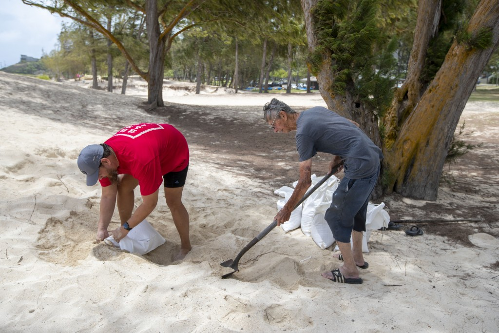 Chris Gomes, left, and John Gomes, right, fill sand bags in preparation of the arrival of Hurricane Douglas in the town of Kailua, Sunday, July 26, 20...