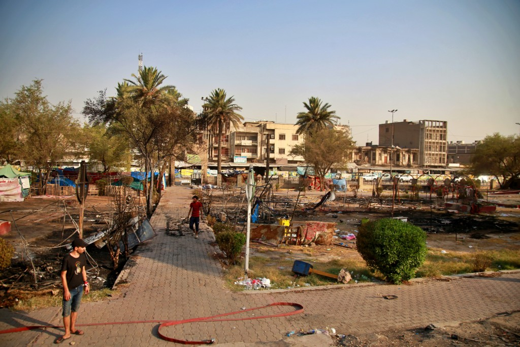 Protesters inspect burned tents near Tahrir Square, Baghdad, Iraq, Monday, July, 27, 2020.  Fresh violence erupted between demonstrators and Iraqi sec...