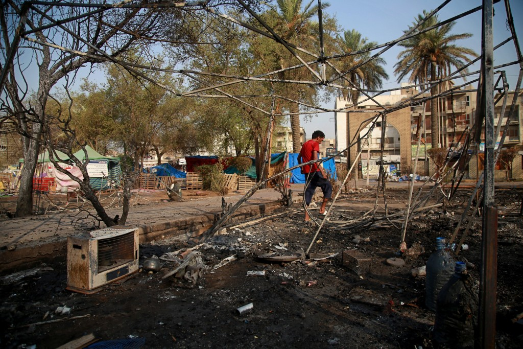 A protester inspects burned tents near Tahrir Square, Baghdad, Iraq, Monday, July, 27, 2020. Fresh violence erupted between demonstrators and Iraqi se...