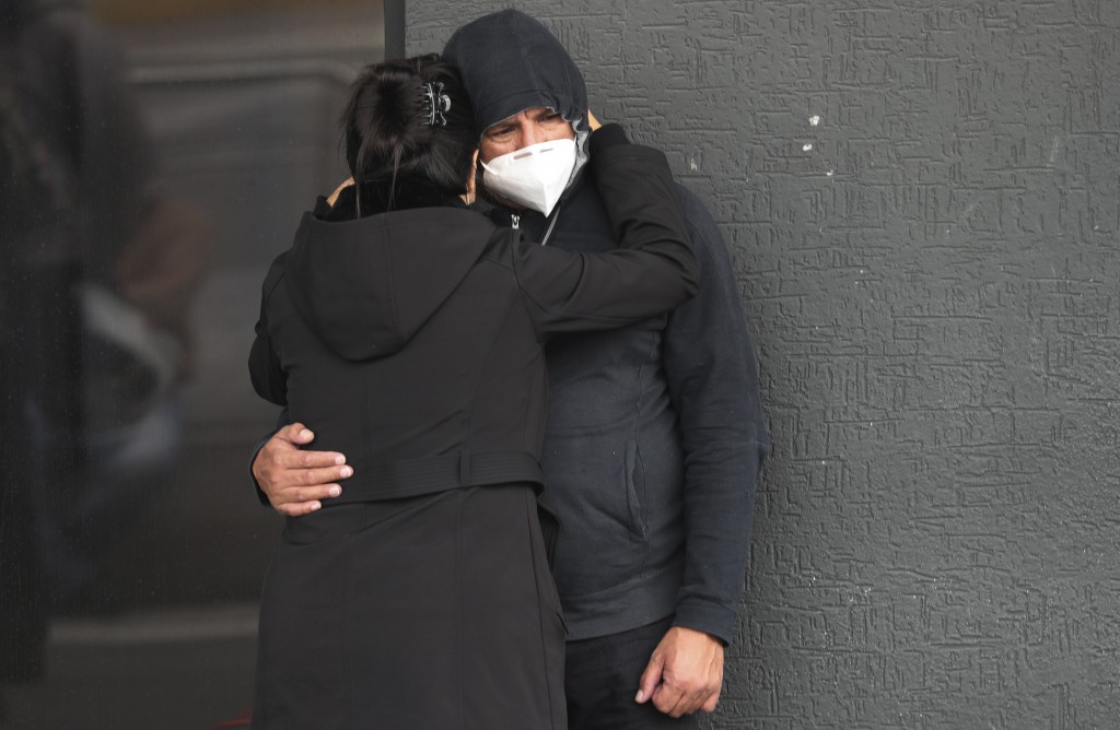 A couple embraces after they were informed that their relative has died from COVID-19, outside of the Instituto de Seguridad Social hospital in Quito,...