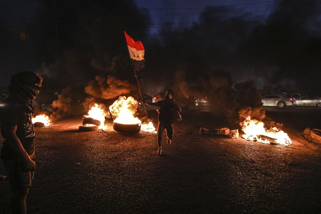 Protesters burn tires during a demonstration demanding better public services and jobs in Basra, southeast of Baghdad, Iraq, Monday, July 27, 2020. (A...