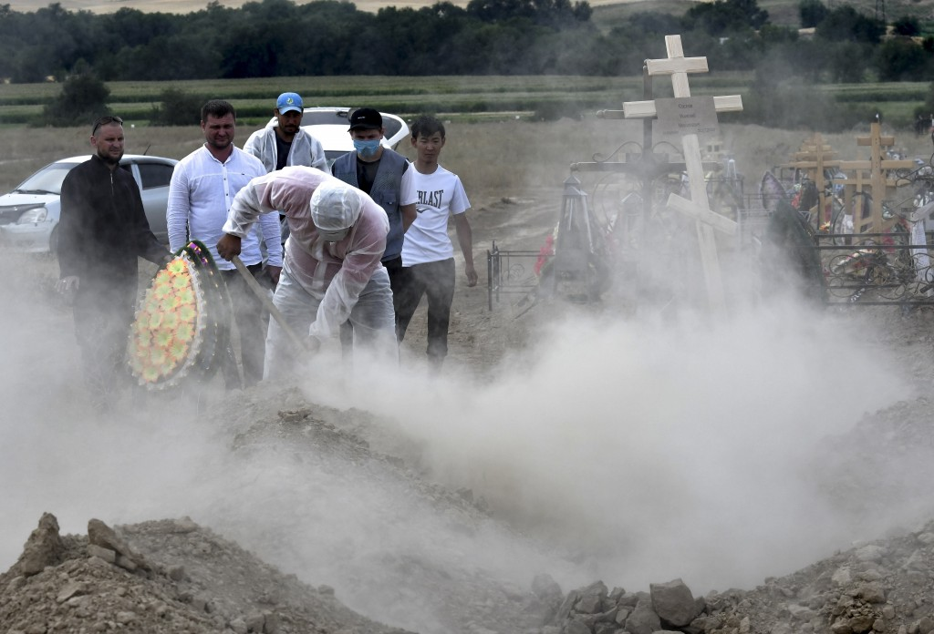 Funeral workers disinfect a grave as they bury the victim of the coronavirus at a cemetery outside Bishkek, Kyrgyzstan, Thursday, July 23, 2020. Coron...