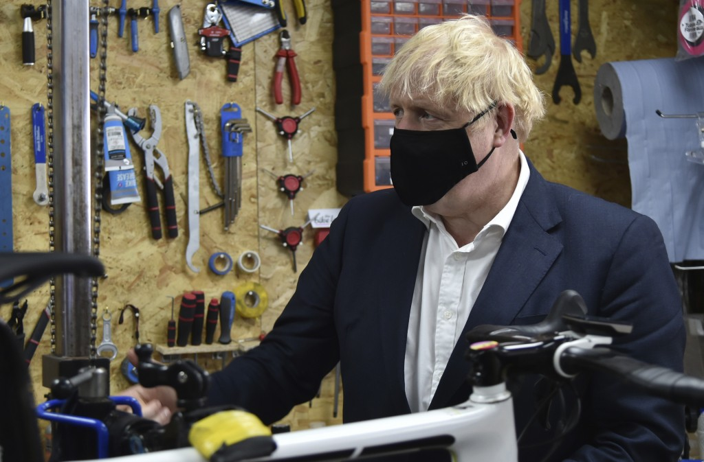 Britain's Prime Minister Boris Johnson talks to the owner of the the Cycle Lounge, Rodney Rouse, a bicycle repair shop Beeston near Nottingham, Englan...