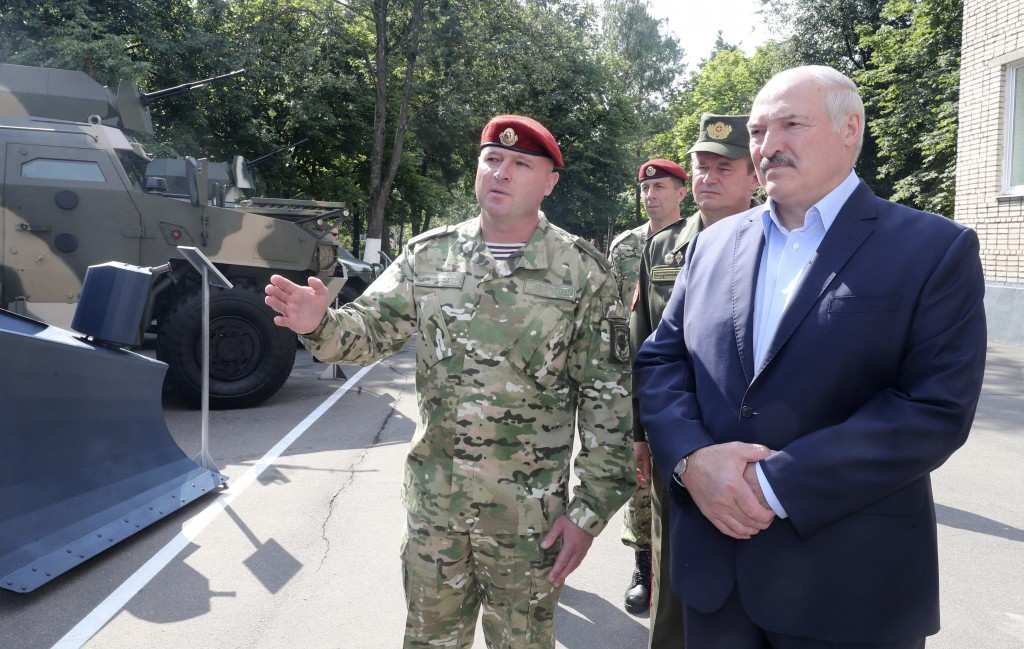 Belarus President Alexander Lukashenko, right, inspects police vehicles as he visits the Belarusian Interior Ministry special forces base in Minsk, Be...