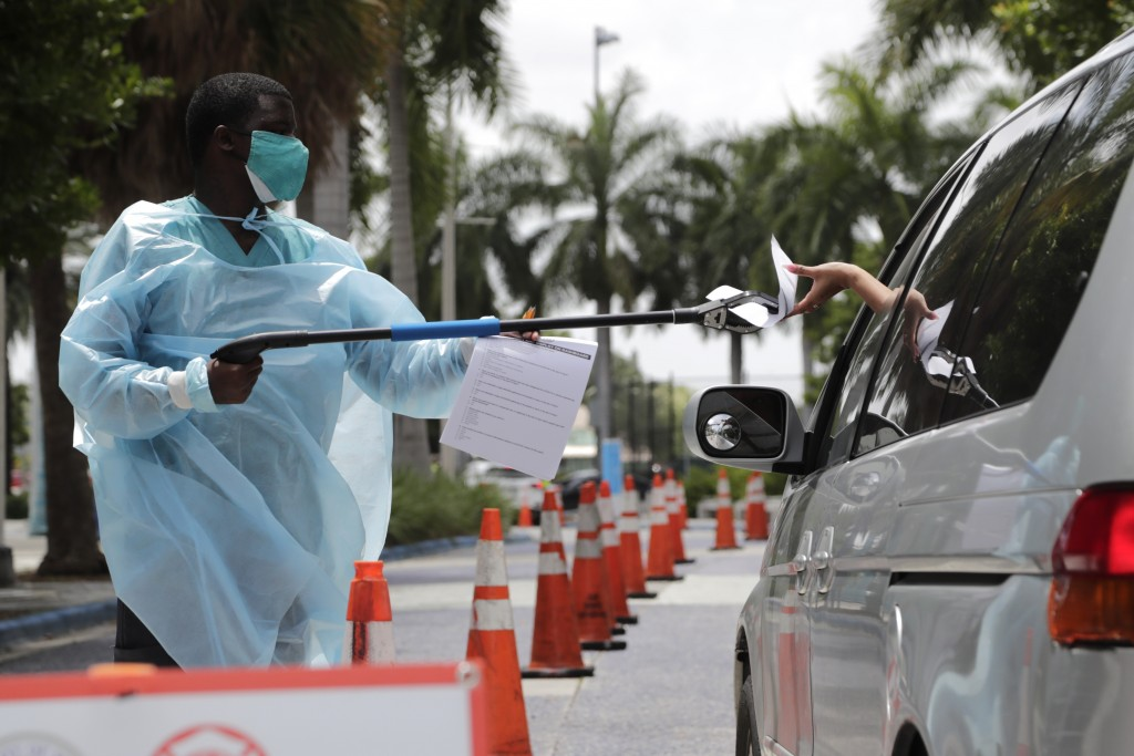 Healthcare worker Dante Hills, left, passes paperwork to a woman in a vehicle at a COVID-19 testing site outside of Marlins Park, Monday, July 27, 202...