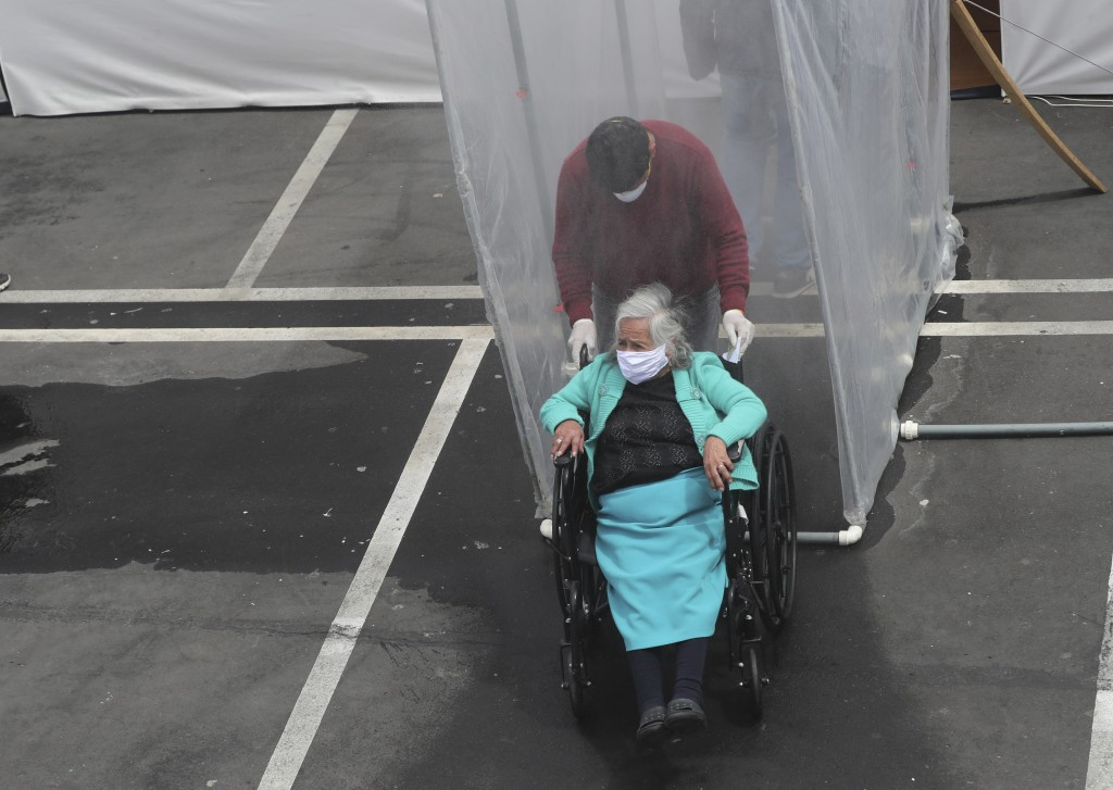 An elderly woman with suspected COVID-19 symptoms is wheeled in by a relative to the Instituto de Seguridad Social for patients with COVID-19 in order...