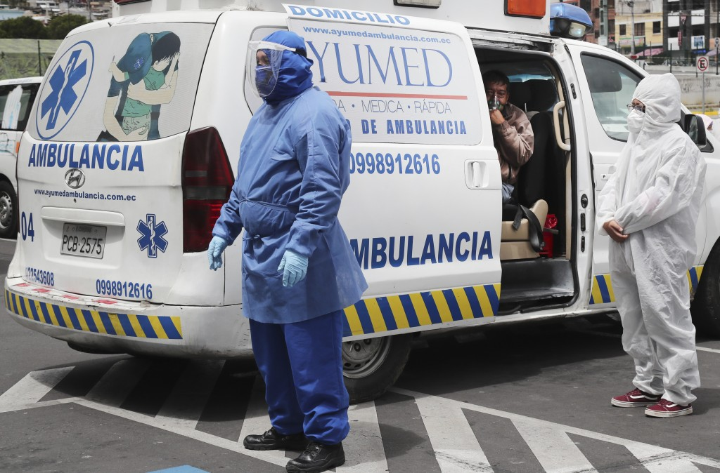 Ambulance personnel wearing protection suits wait for a patient with COVID-19 symptoms to be admitted to the Instituto de Seguridad Social hospital in...