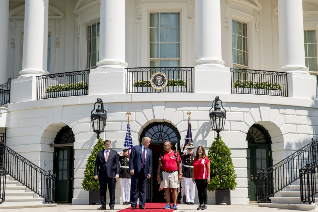 President Donald Trump, Veterans Affairs Secretary Robert Wilkie, left, and Karen Pence, the wife of Vice President Mike Pence, right, pose for photog...