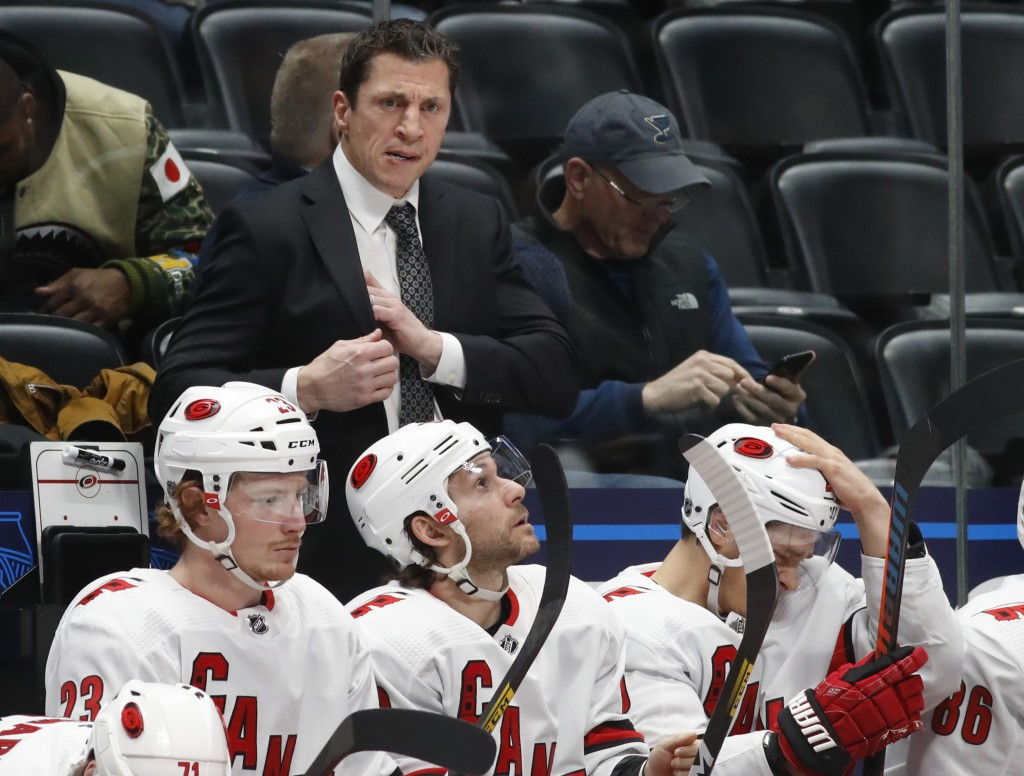 FILE - In this Dec. 19, 2019, file photo, Carolina Hurricanes coach Rod Brind'Amour stands behind players during the second period of an NHL hockey ga...