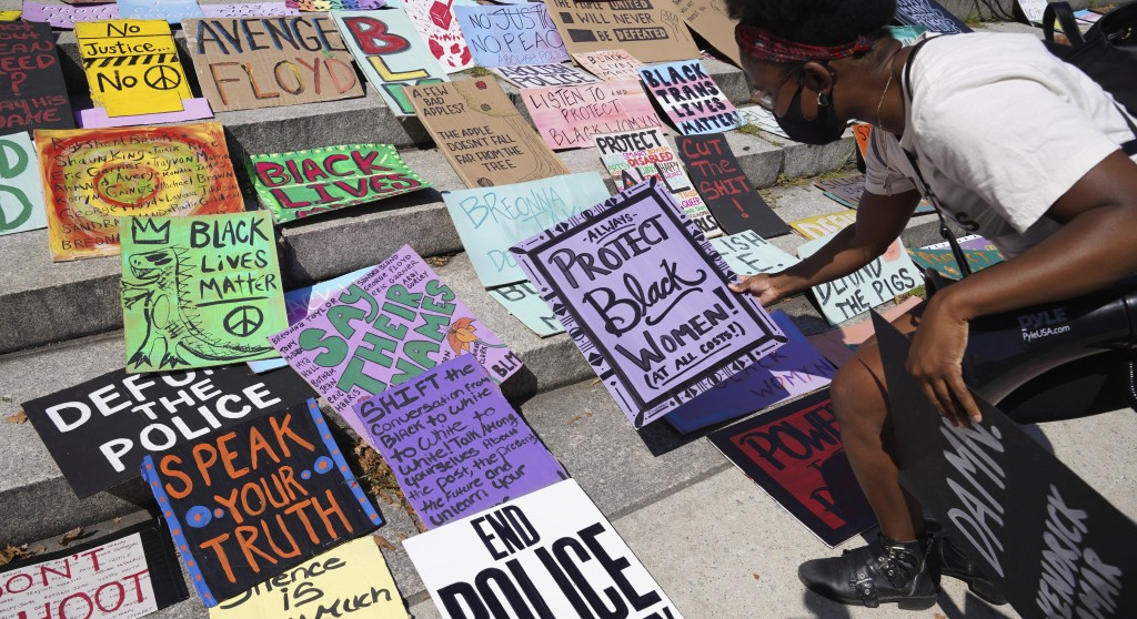 EDS NOTE: OBSCENITY - Activist and minister Kianna Ruff chooses a placard to carry ahead of a protest against police brutality and systemic racism on ...