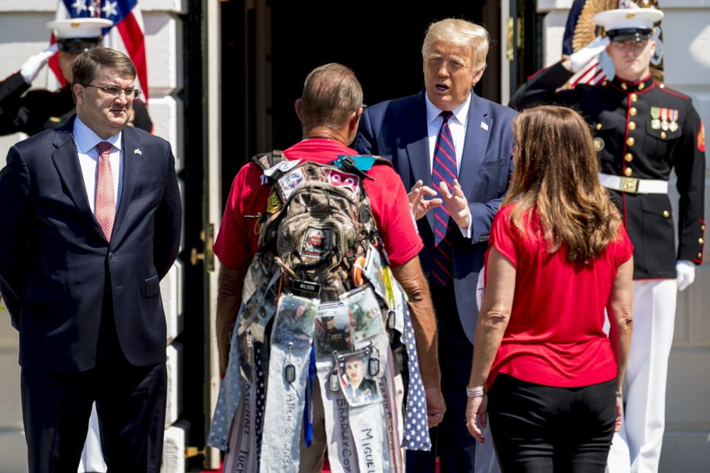 President Donald Trump, accompanied by Veterans Affairs Secretary Robert Wilkie, left, and Karen Pence, the wife of Vice President Mike Pence, right, ...