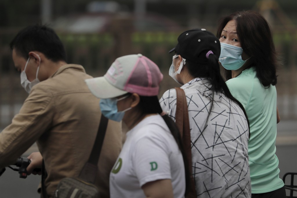 People wearing a face mask wait to cross a street in Beijing, Tuesday, July 28, 2020. New coronavirus cases continue to rise in China's northwestern r...