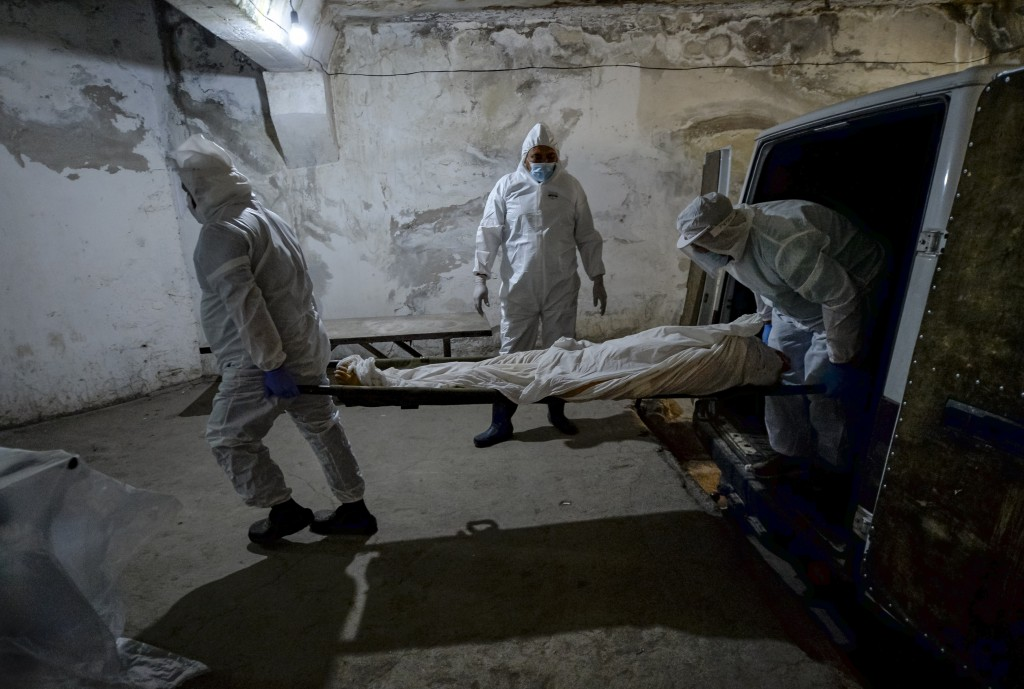 Pathologists in protective suits transport the body of a person who died of the coronavirus at a hospital's morgue in Bishkek, Kyrgyzstan, Wednesday, ...