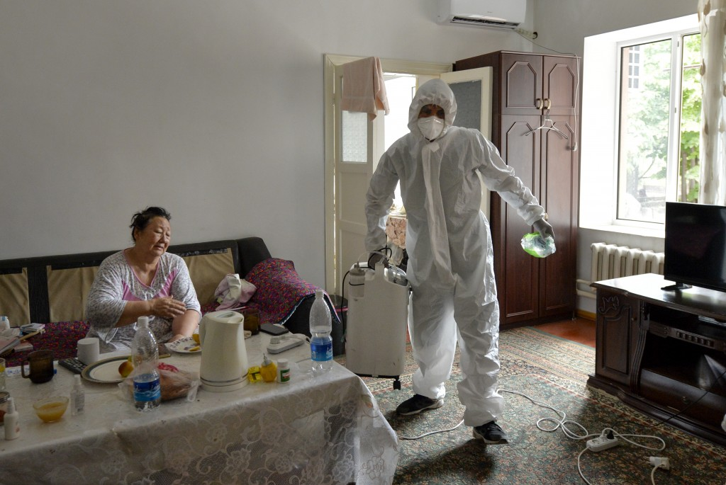 A volunteer in protective suit and gloves carries an oxygen concentrator to help a suspected coronavirus patient breathe at her apartment in Bishkek, ...