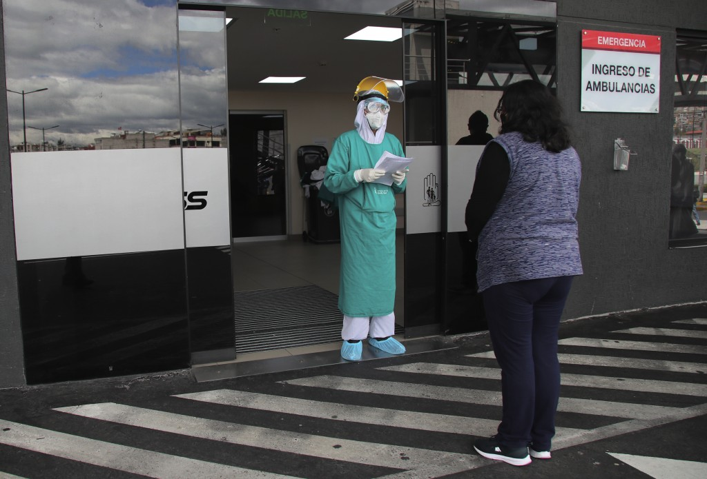 A doctor informs a woman about the condition of her relative who was admitted with COVID-19 to the Seguridad Social hospital in Quito, Ecuador, Monday...