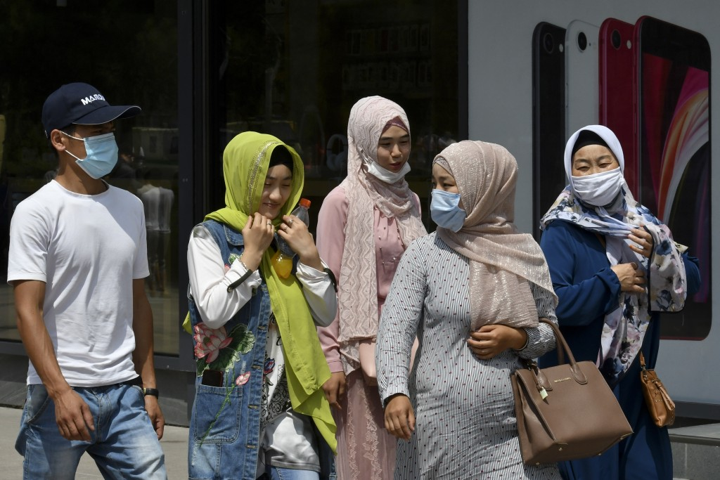 People in face masks walk through a street in Bishkek, Kyrgyzstan, Friday, July 24, 2020. Coronavirus cases surged in Kyrgyzstan after authorities lif...