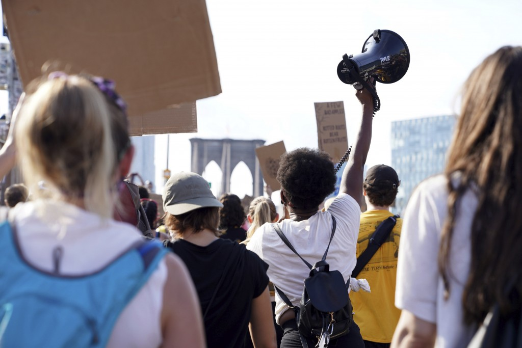 Activist and minister Kianna Ruff raises a megaphone as she and hundreds of others cross the Brooklyn Bridge to protest police brutality and systemic ...