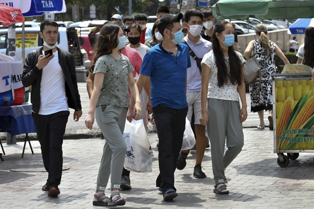 Youths in face masks walk through a street market in Bishkek, Kyrgyzstan, Friday, July 24, 2020. Coronavirus cases surged in Kyrgyzstan after authorit...