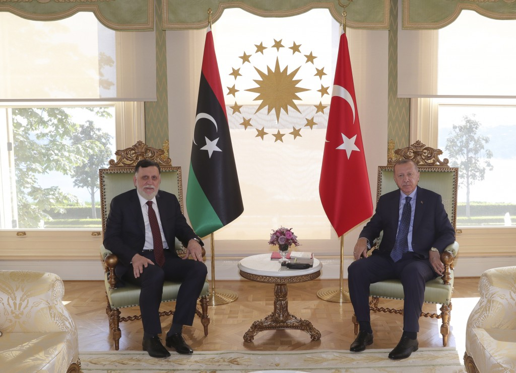 FILE - In this Saturday, July 25, 2020 file photo, Turkey's President Recep Tayyip Erdogan, right, and Fayez Sarraj, the head of Libya's international...