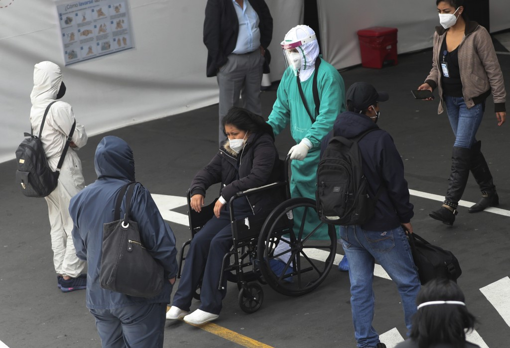 A woman is admitted to the Instituto del Seguro Social hospital for patients with COVID-19, in Quito, Ecuador, Monday, July 27, 2020. (AP Photo/Dolore...