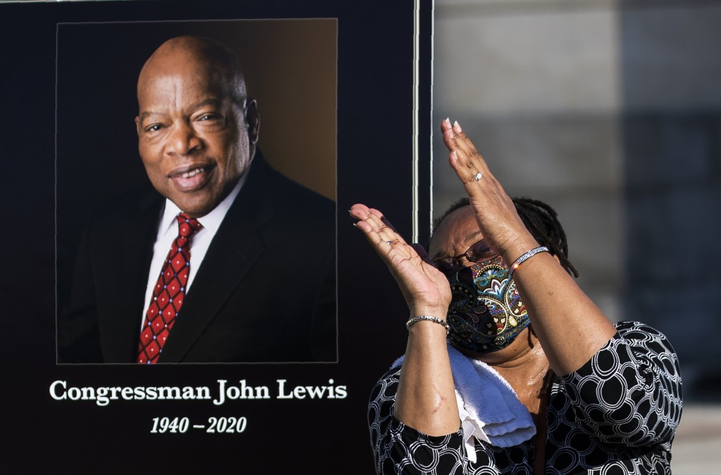 Jaquenette Ferguson from Oxon Hill, Md., gestures as she gets her picture taken beside a portrait of the late Rep. John Lewis, D-Ga., near the East Fr...