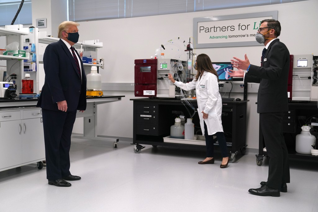 Fujifilm Diosynth Biotechnologies CEO Martin Meeson, right, speaks as President Donald Trump wears a face mask as he participates in a tour of Bioproc...