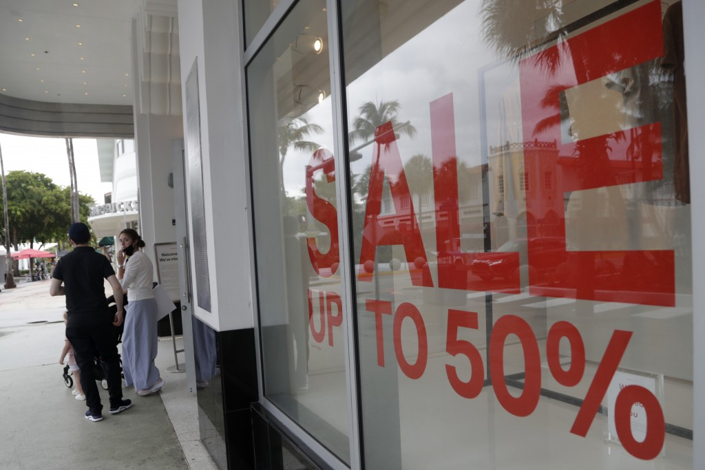 FILE - In this June 17, 2020 file photo, a sign advertises a sale at an H&M store along Lincoln Road Mall in Miami Beach, Fla.    U.S. consumer confid...
