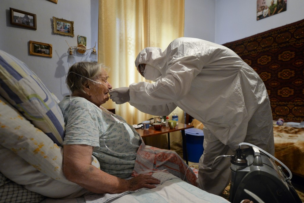 A volunteer in a protective suit and gloves sets an oxygen concentrator to help a suspected coronavirus patient breathe at her apartment in Bishkek, K...