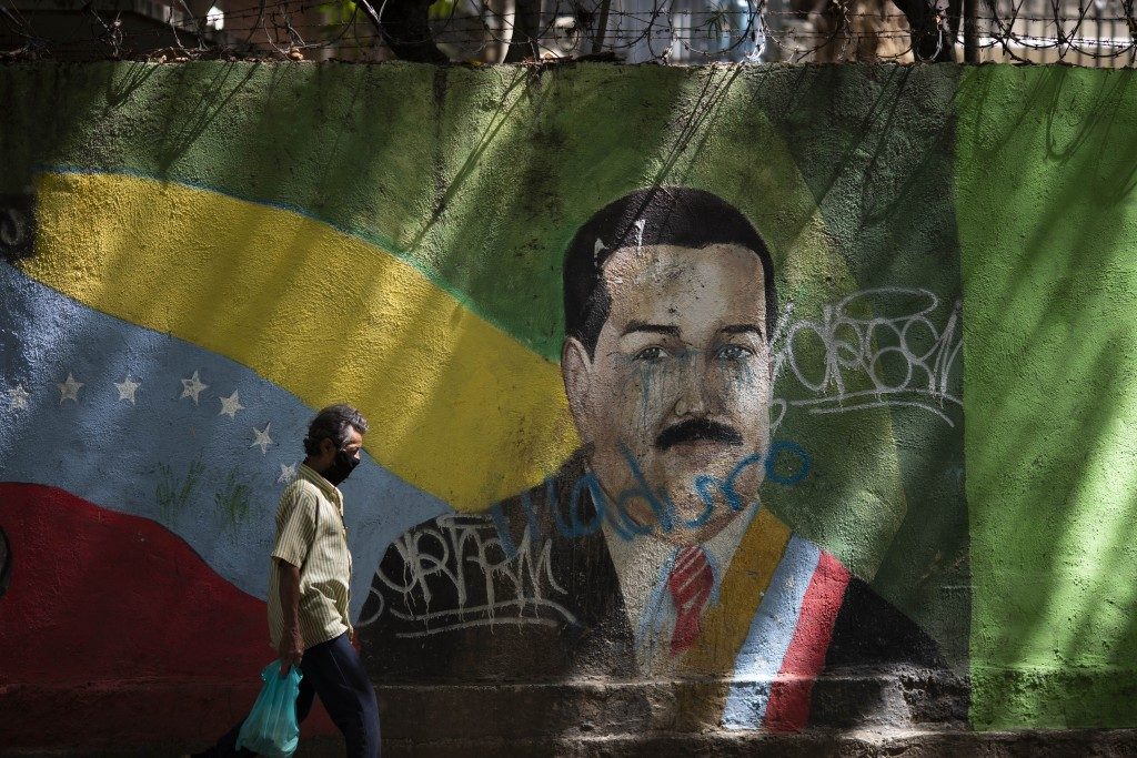 A man wearing a face mask amid the COVID-19 pandemic passes a mural of Venezuelan President Nicolas Maduro in Caracas, Venezuela, Wednesday, July 22, ...
