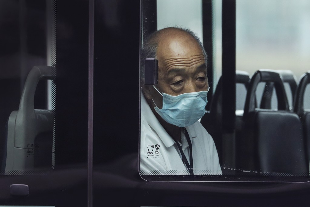A man wearing a face mask to protect against the new coronavirus rides alone on a bus in Beijing, Tuesday, July 28, 2020. New coronavirus cases contin...