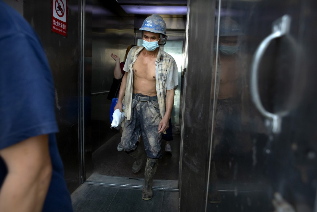 A construction worker wearing a face mask to protect against the coronavirus walks out of an elevator in Beijing, Wednesday, July 29, 2020. China repo...