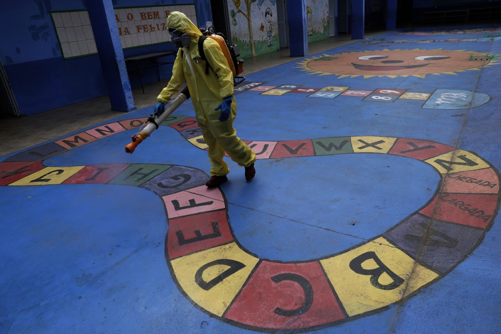 A government employee disinfects a public school as a measure against the spread of the new coronavirus, in the Taguatinga neighborhood of Brasilia, B...