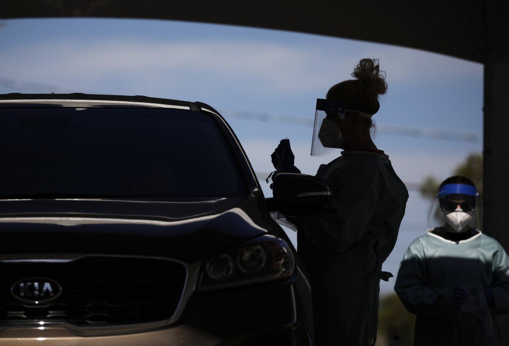 FILE - In this July 10, 2020, file photo healthcare workers test patients in their cars at a drive-thru coronavirus testing site in Las Vegas. (AP Pho...