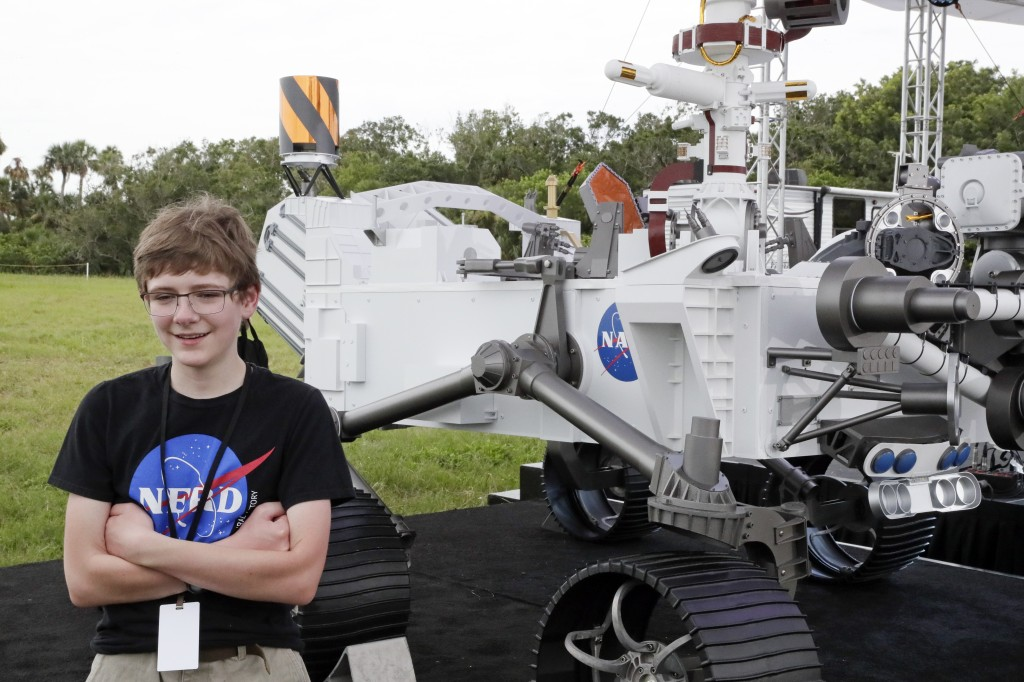 Alexander Mather, of Burke, Va. stands next to a model of the Mars 2020 rover he named in a contest during a news conference at the Kennedy Space Cent...