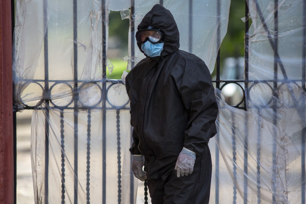A funeral home worker wearing a full protective gear to protect himself from the spread of the new coronavirus waits to enter La Verbena cemetery in G...