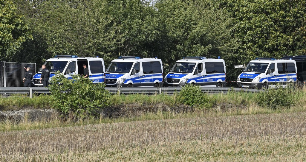 Germany police vehicles parked during a search at an allotment garden plot in Seelze, near Hannover, Germany, Tuesday July 28, 2020. Police have begun...
