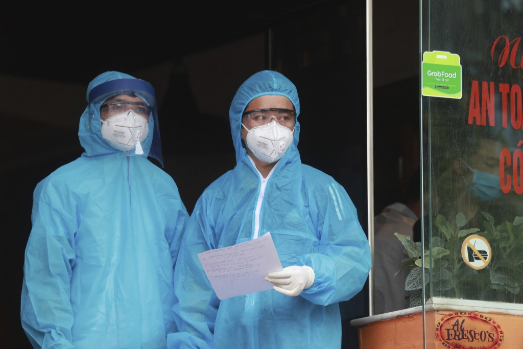 Health workers look out from a restaurant where a worker is suspected to have COVID-19 in Hanoi, Vietnam on Wednesday, July 29, 2020. Vietnam intensif...