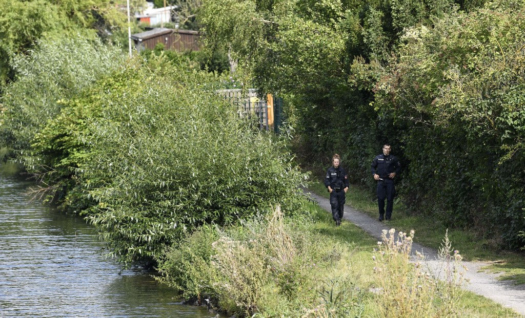 German police officers walk along a canal during an investigation at an allotment garden plot in Seelze, near Hannover, Germany, Tuesday July 28, 2020...