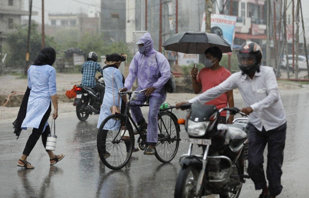 People wear face masks and move through a street in the rain in Prayagraj, India, Wednesday, July 29, 2020. India is the third hardest-hit country by ...
