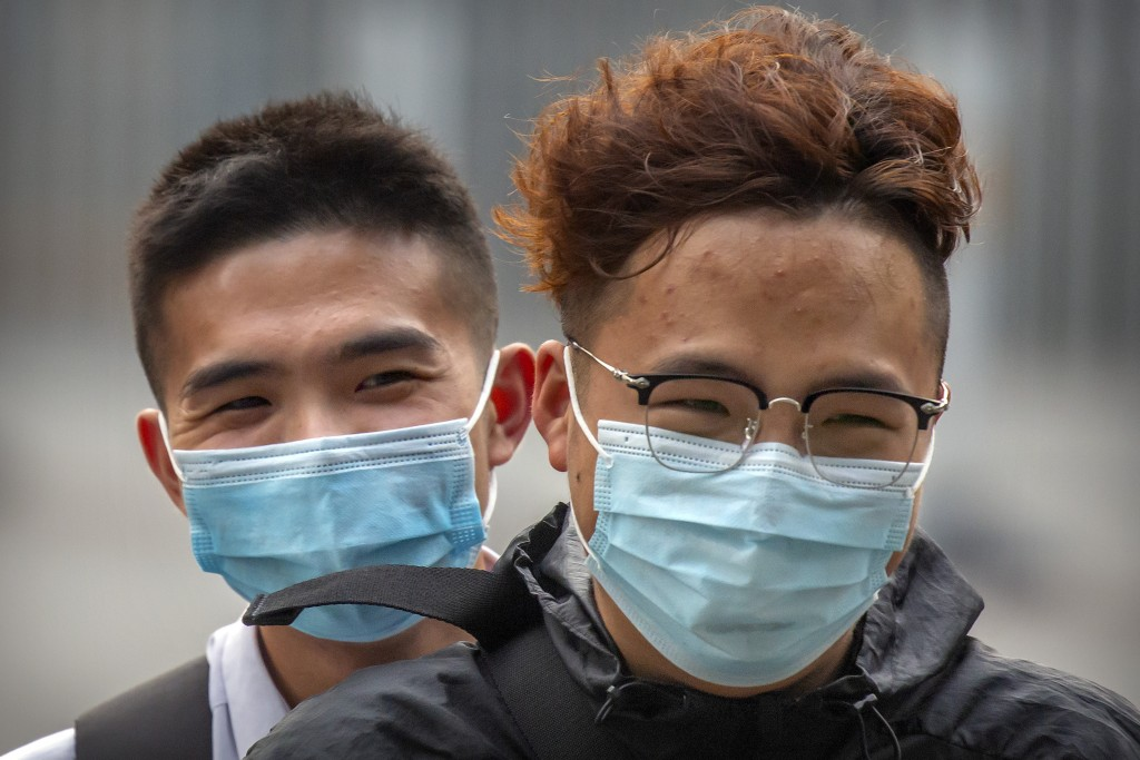 People wearing face masks to protect against the coronavirus ride a motor scooter in Beijing, Wednesday, July 29, 2020. China reported more than 100 n...