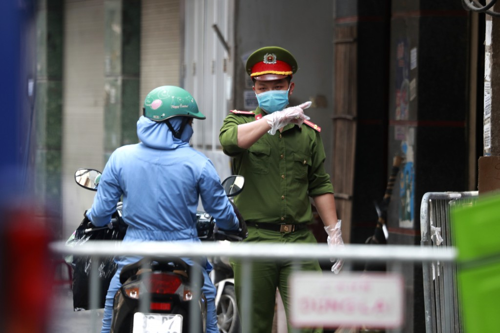 A police officer talks to a woman at the barricaded entrance of an alley where one of its residents has COVID-19 in Hanoi, Vietnam on Wednesday, July ...