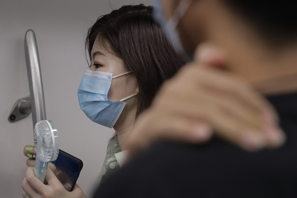 A woman wearing a face mask to protect against the new coronavirus uses an electric fan to cool herself as she rides in a subway train in Beijing, Wed...