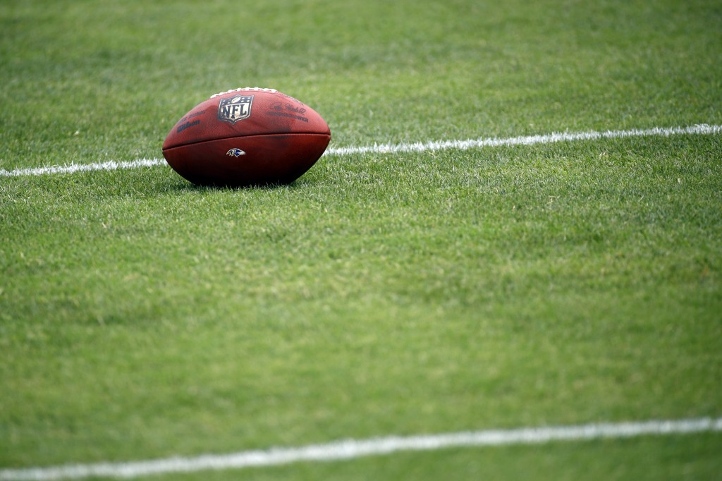 FILE - In this July 28, 2017, file photo, a football sits on a Baltimore Ravens practice field during NFL football training camp in Owings Mills, Md. ...